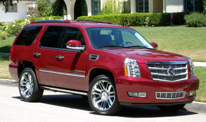 A three-quarter front view of a red 2011 Cadillac Escalade Hybrid