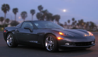 A three-quarter front view of a black 2009 Chevrolet Corvette Coupe in the moonlight