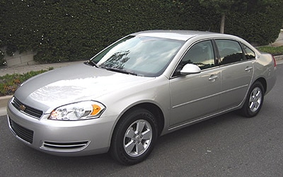 A three-quarter front view of a gray 2006 Chevrolet Impala LT