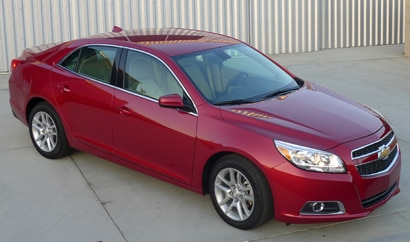 A three-quarter front view of a red 2013 Chevrolet Malibu Eco