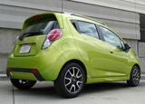 A three-quarter rear view of a green 2013 Chevrolet Spark