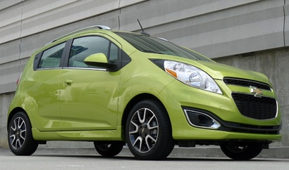 A three-quarter front view of a Jalapeño green 2013 Chevrolet Spark 2LT