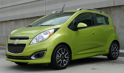A three-quarter front view of a green Chevrolet Spark