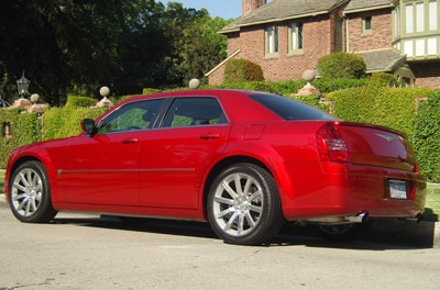 A three-quarter rear view of a red Chrysler 300C SRT8