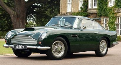 A three-quarter front view of a green 1959 Aston Martin DB4 GT