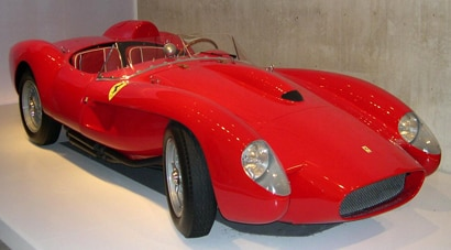A three-quarter front view of a red 1958 Ferrari 250 TR
