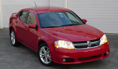 A three-quarter front view of a red 2012 Dodge Avenger SXT Plus