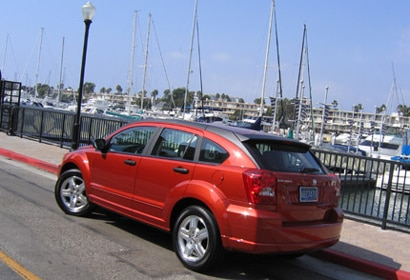 A three-quarter rear view of a red 2006 Dodge Caliber SXT Sport by a marina