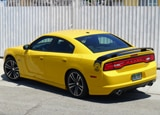 A three-quarter rear view of a yellow 2012 Dodge Charger SRT8 Super Bee