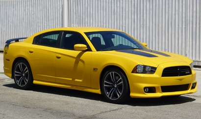 A three-quarter front view of a yellow 2012 Dodge Charger SRT8 Super Bee