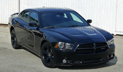 A three-quarter front view of a black 2012 Dodge Charger SXT Plus