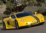 A three-quarter front view of a yellow Ascari A10 in action