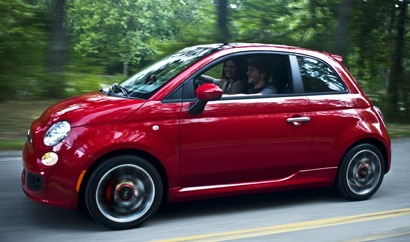 A side view of a red Fiat 500 in action