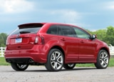A three-quarter rear view of a red 2011 Ford Edge Sport