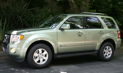 A three-quarter front view of a light green 2009 Ford Escape Hybrid
