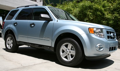 A three-quarter front view of a light blue 2009 Ford Escape Hybrid