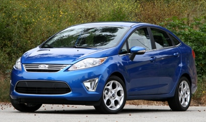 A three-quarter front view of a blue 2011 Ford Fiesta sedan