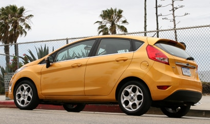 A three-quarter rear view of a yellow 2011 Ford Fiesta
