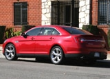 A three-quarter rear view of a red 2010 Ford Taurus SHO