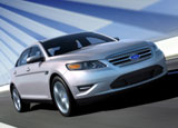 A three-quarter front view of a silver 2010 Ford Taurus