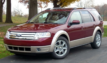 A three-quarter front view of a maroon 2008 Ford Taurus X AWD Eddie Bauer