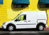 A side view of a white 2010 Ford Transit Connect XLT