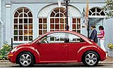 A side view of a red Volkswagen New Beetle TDI