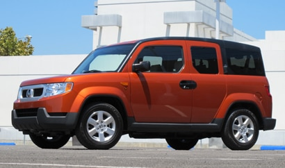 A three-quarter front view of an orange 2010 Honda Element 4WD EX
