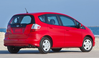 A three-quarter rear view of a red 2012 Honda Fit