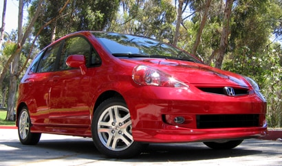 A three-quarter front view of a red 2009 Honda Fit