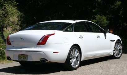 A three-quarter rear view of a white 2011 Jaguar XJL
