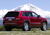A three-quarter rear view of a red 2011 Jeep Grand Cherokee