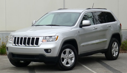 A three-quarter front view of a silver 2011 Jeep Grand Cherokee Laredo