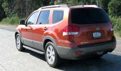A three-quarter rear view of a metallic orange 2009 Kia Borrego EX