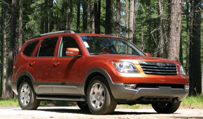A three-quarter front view of a metallic orange 2009 Kia Borrego EX