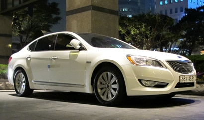 A three-quarter front view of a silver 2011 Kia Cadenza in action