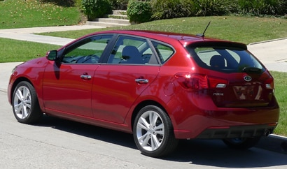 A three-quarter rear view of a red 2011 Kia Forte 5-Door SX
