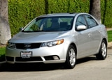 A three-quarter front view of a silver 2010 Kia Forte