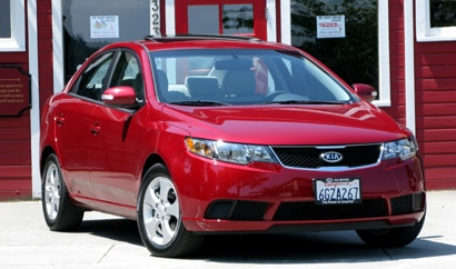 A three-quarter front view of a red 2010 Kia Forte Ex