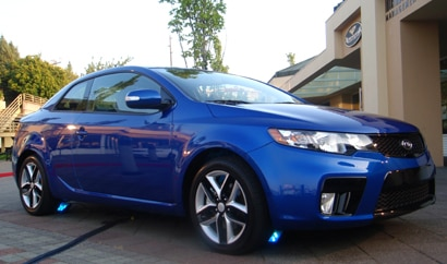 A three-quarter front view of a blue 2010 Kia Forte Koup