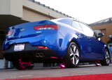 A three-quarter rear view of a blue 2010 Kia Forte Koup