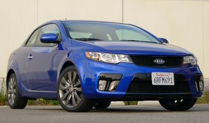 A three-quarter front view of a blue 2011 Kia Forte SX Koup