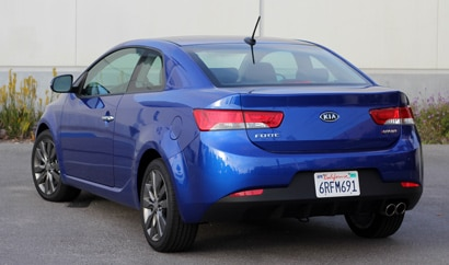 A three-quarter rear view of a blue 2011 Kia Forte Koup SX