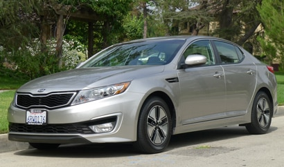 A three-quarter front view of a silver Kia Optima Hybrid