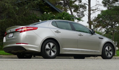 A three-quarter rear view of a silver 2012 Kia Optima Hybrid