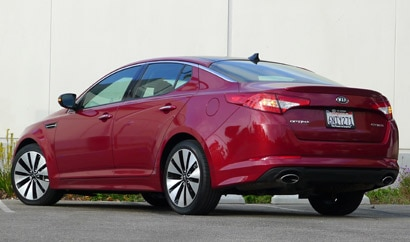 A three-quarter rear view of a red 2012 Kia Optima SX Turbo