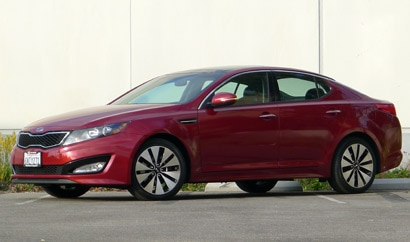 A three-quarter front view of a red 2012 Kia Optima SX Turbo