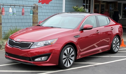 A three-quarter front view of a red 2011 Kia Optima