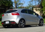 A three-quarter rear view of a silver 2012 Kia Rio 5-Door SX