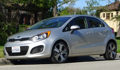 A three-quarter front view of a silver 2012 Kia Rio 5-Door SX